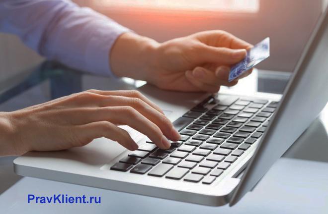 Мужчина расплачивается за покупки в интернете банковской карточкой