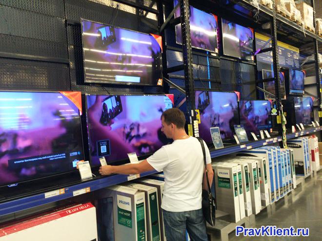 Мужчина выбирает телевизор в магазине