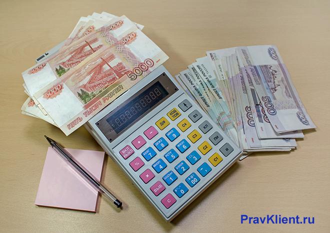 Калькулятор, денежные купюры лежат на столе
