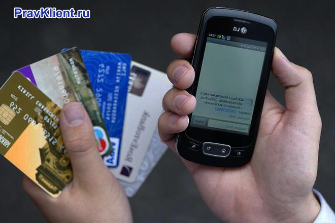 Мужчина держит в одной руке банковские карточки и телефон