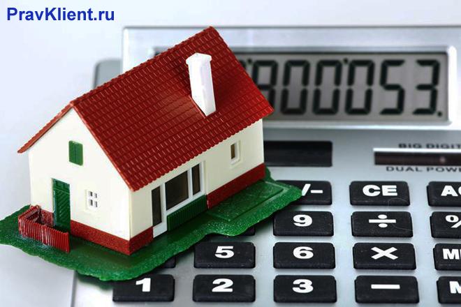 Макет дома стоит на клавишах калькулятора