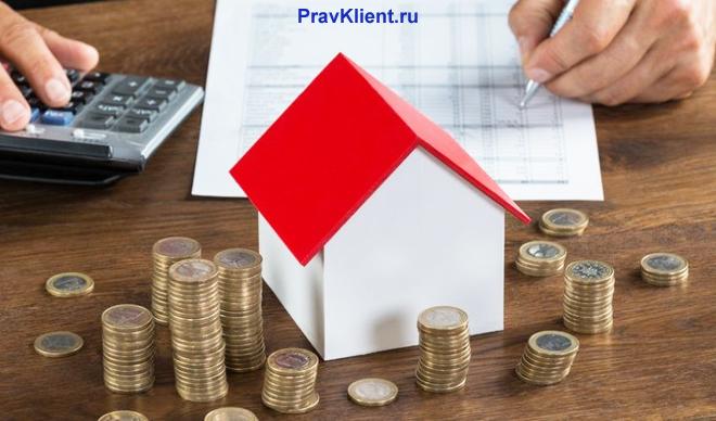 Домик с красной крышей, стопки из монет, калькулятор
