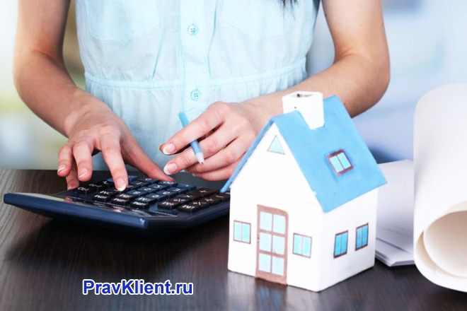 Девушка считает на калькуляторе, рядом стоит на столе бумажный домик