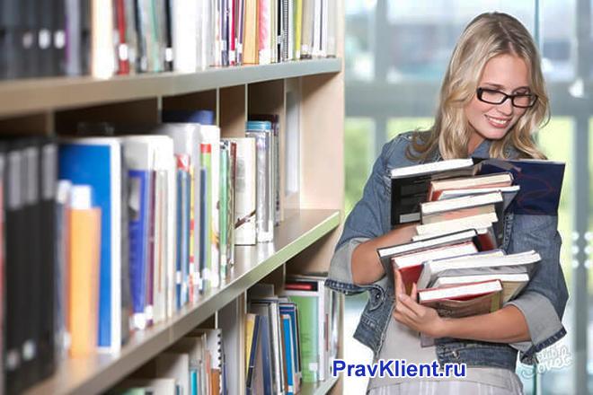 Девушка берет книги в библиотеке