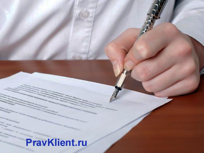 Мужчина в белой рубашке сидит за столом и пишет заявление