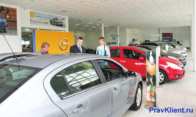 В автосалоне покупатели смотрят машину