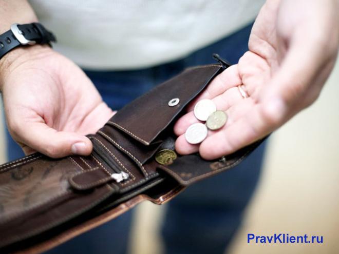 Мужчина достает последние монеты из кошелька
