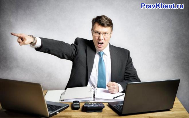 Рассерженный мужчина сидит за ноутбуком