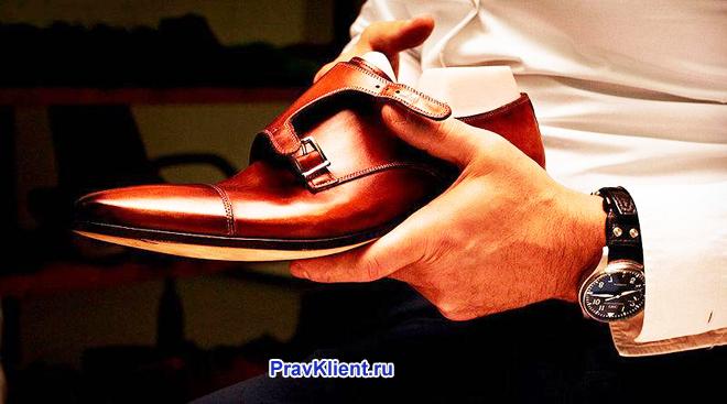 Мужчина держит в руке ботинок