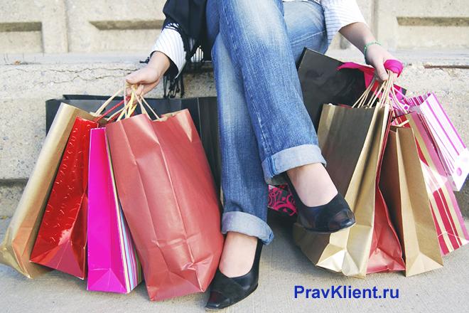 Девушка сидит с покупками