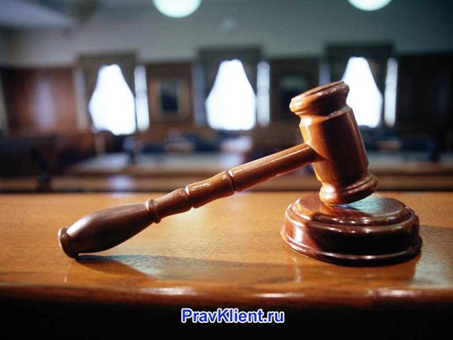 Молоточек лежит на фоне зала судебных заседаний