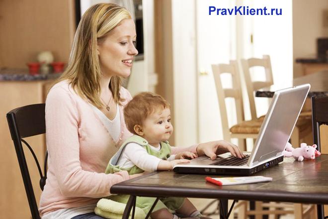 Девушка сидит за ноутбуком с ребенком