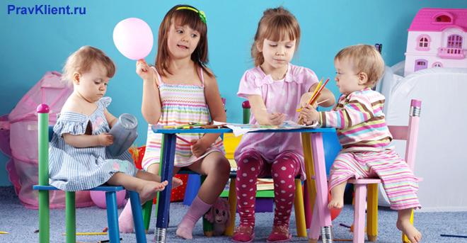 Четыре девочки рисуют, сидя за столом