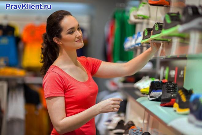 Продавец расставляет обувь на стеллаже в магазине