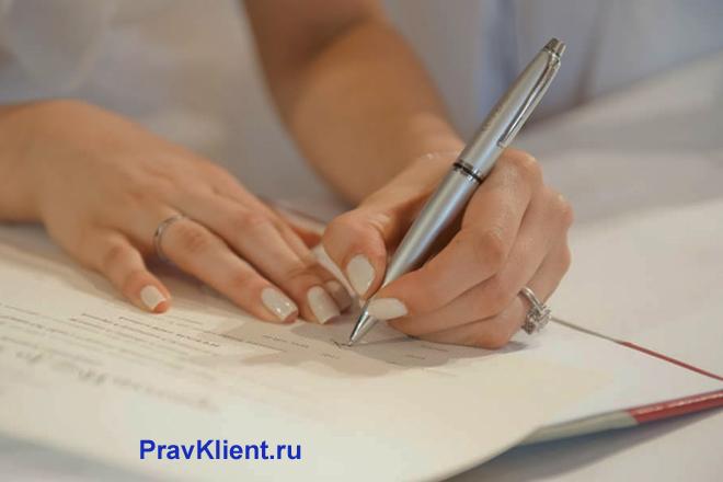 Девушка пишет в тетради ручкой