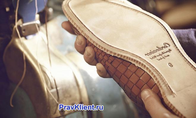 Мужчина осматривает подошву обуви