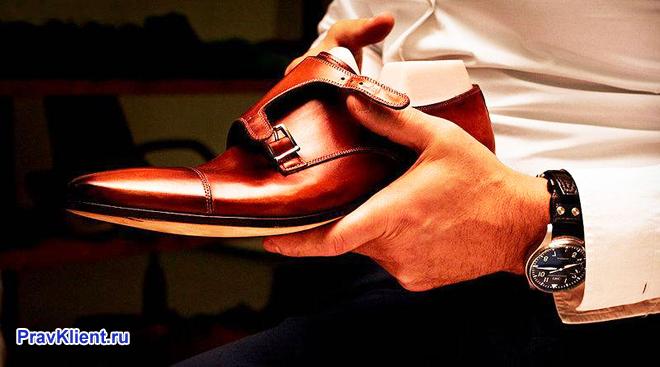 Мужчина в белой рубашке держит в руке ботинок