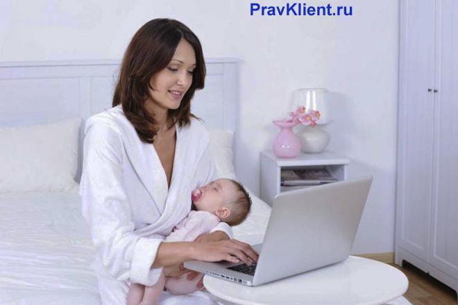 Молодая мама сидит на кровати с ребенком и смотрит в ноутбук