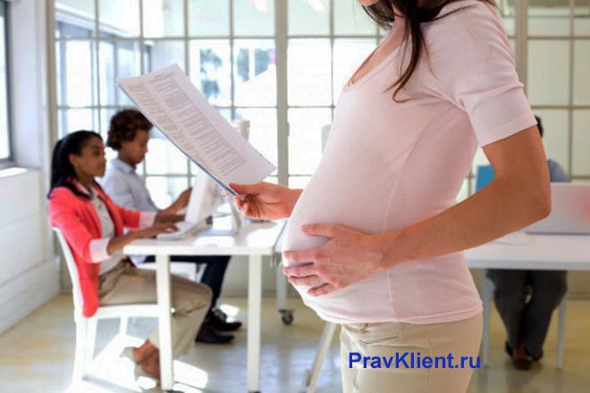 Беременная женщина читает документы на фоне детей