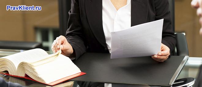 Бизнес-леди записывает информацию из книги