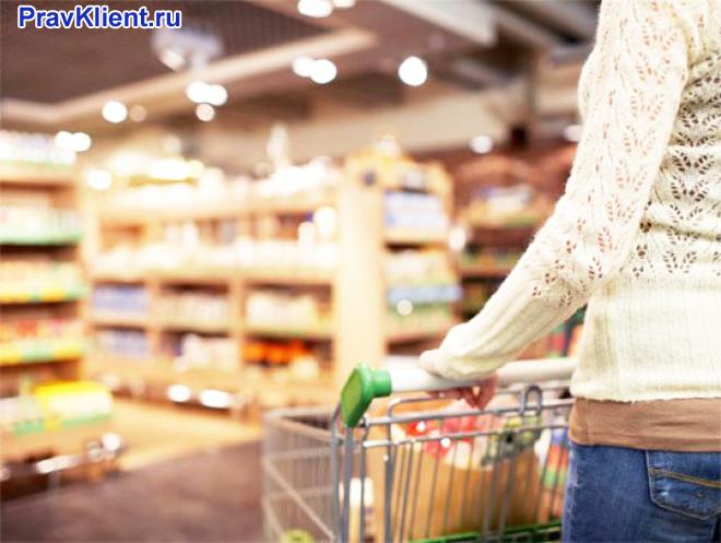 Девушка покупает продукты у супермаркете