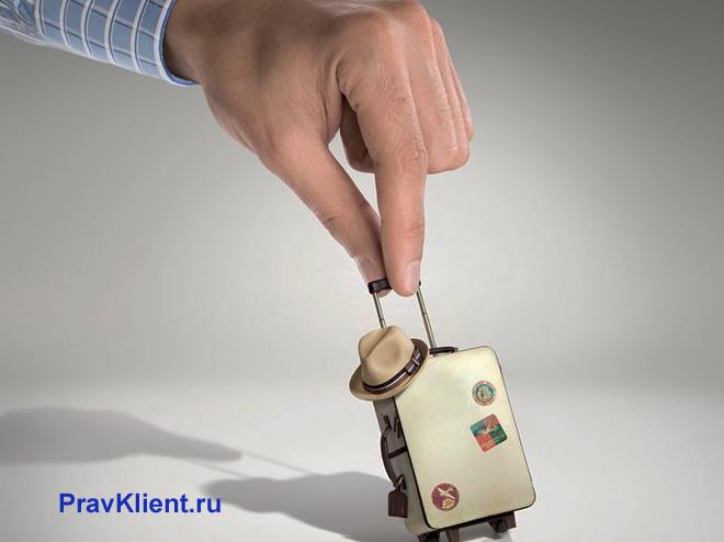 Мужчина держит в руке чемодан