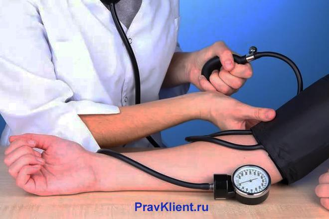 Медсестра измеряет давление мужчине