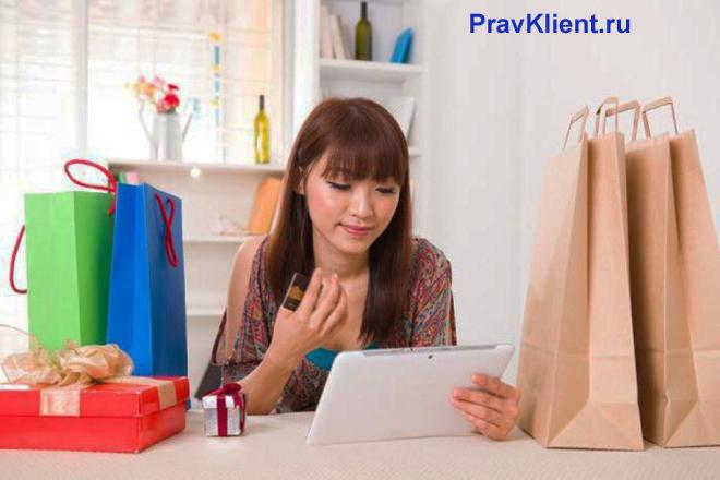 Девушка читает документ, рядом стоят покупки из магазина