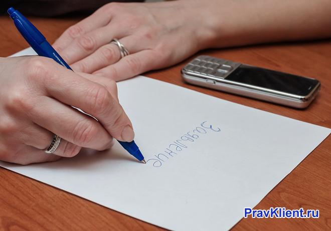 Девушка пишет заявление на столе
