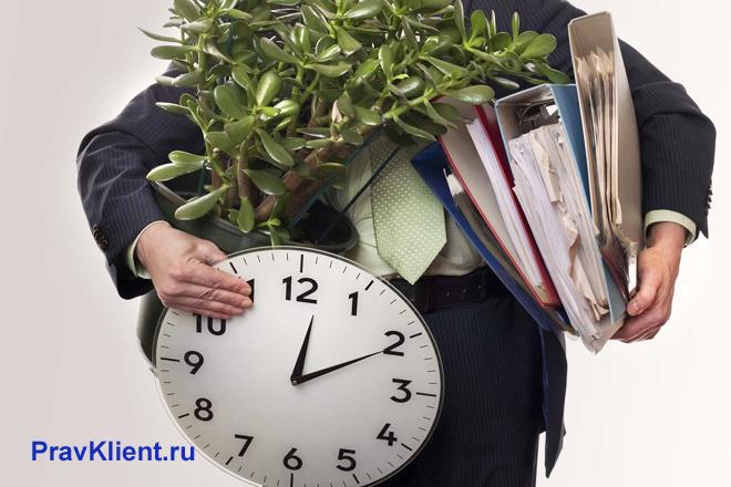 Офисный работник несет в руках свои вещи
