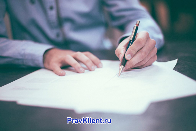 Мужчина в синей рубашке пишет на листке бумаги