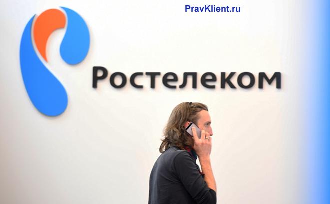Мужчина разговаривает на фоне логотипа Ростелекома