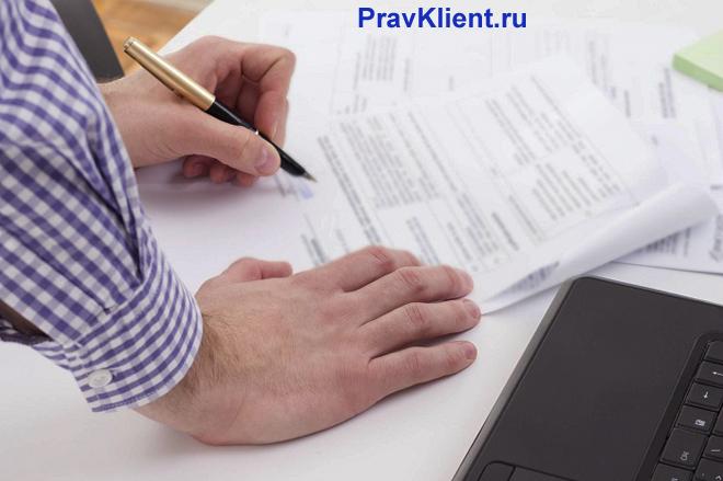Мужчина в клетчатой рубашке пишет заявление рядом с ноутбуком