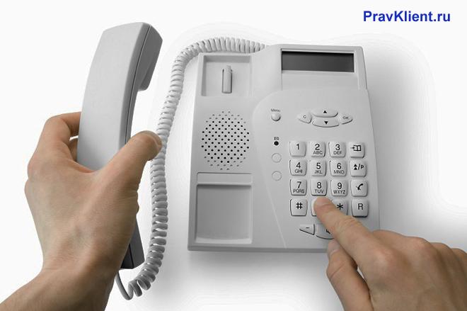 Мужчина набирает номер на стационарном телефоне