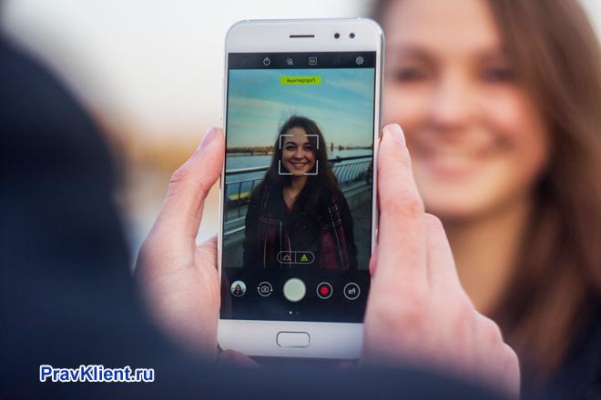 Девушку фотографируют на камеру смартфона