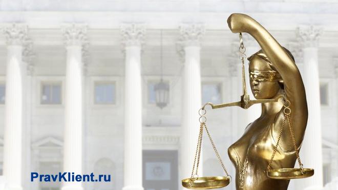 Золотая статуэтка Фемиды стоит на фоне здания с колоннами