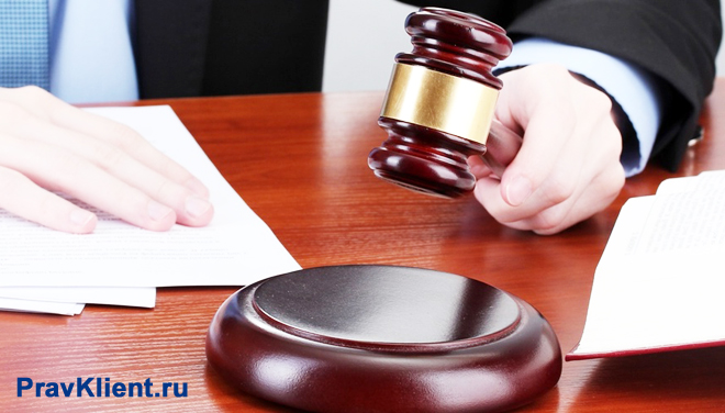 Судья держит в руке деревянный молоточек