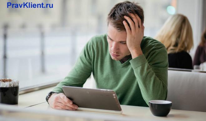 Мужчина держит в руке планшет и пьет чай в кафе