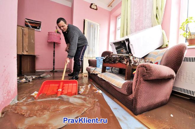 Мужчина убирает квартиру после потопа