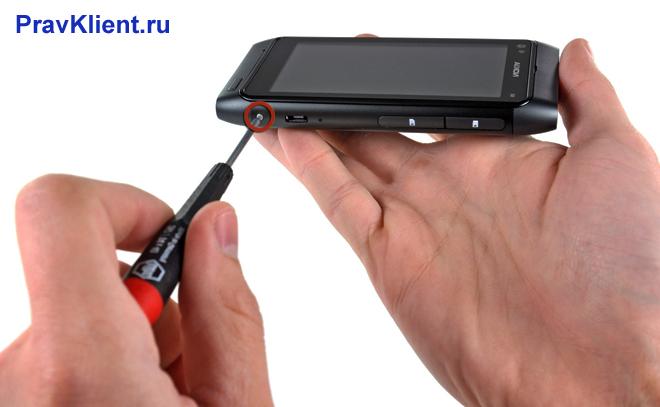 Мужчина вскрывает корпус мобильного телефона