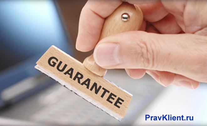 Человек держит в руке штамп с гарантией