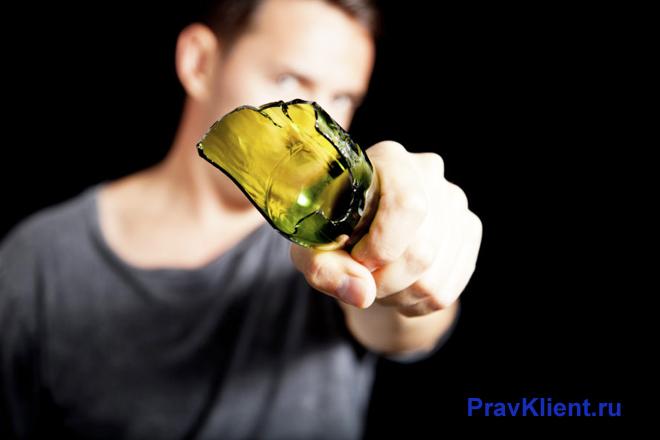 Мужчина держит перед собой разбитую бутылку