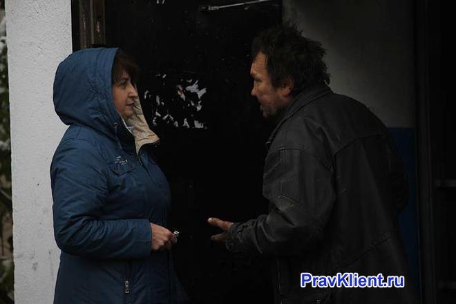 Женщина разговаривает с соседом в подъезде