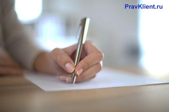 Девушка пишет ручкой металлического цвета на листке бумаги