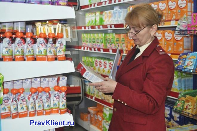 Сотрудница Роспотребнадзора проверяет витрину магазина