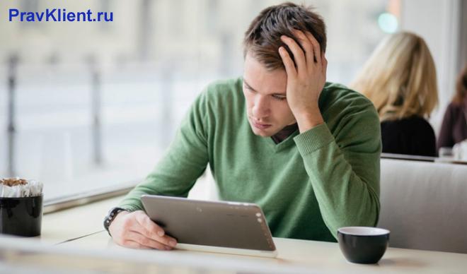 Мужчина сидит с планшетом в общественном месте