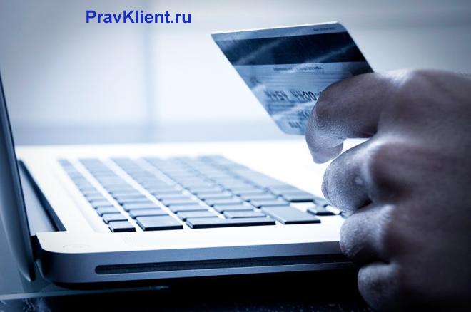 Мужчина делает покупки с помощью банковской карты в интернете