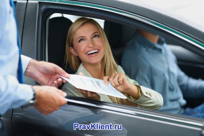 Девушка в машине забирает документ из рук мужчины