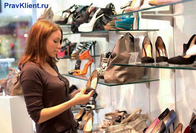 Девушка сморит обувь на витрине магазина