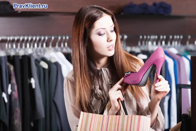 Девушка рассматривает в магазине розовую туфлю